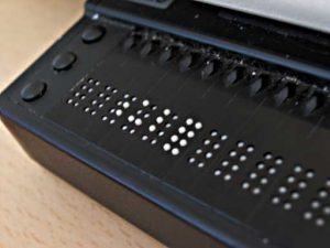 A refreshable braille device sits atop a table. The black, plastic display shows ten braille cells, of white four feature brailled characters.