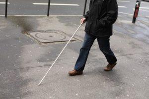 Man walking on sidewalk with a white cane.