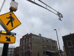 A pedestrian walking sign and overhead lights with sky in the background.