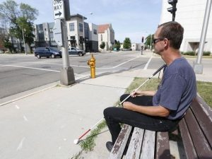 Man with cane sitting on bench next to intersection