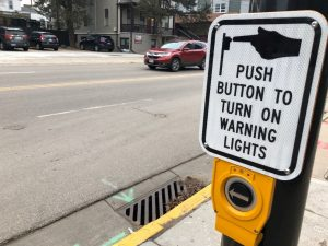"""A sign reading """"push button to turn on warning lights"""" mounted above a button on a street light."""