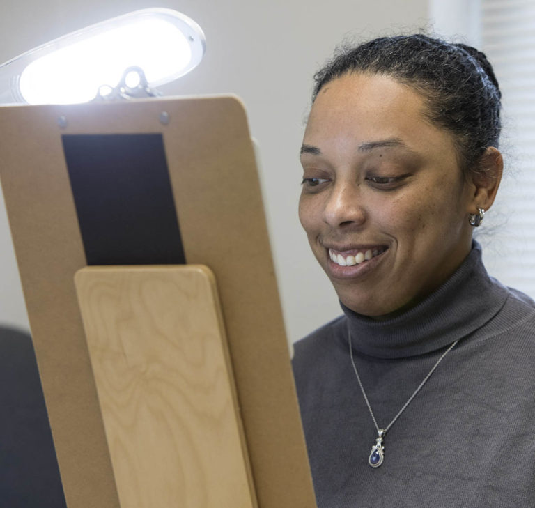A woman looks at a clipboard with a bright light shining on it