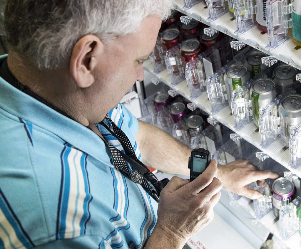 A BEP owner stocks a vending machine full of cans using an adaptive device.