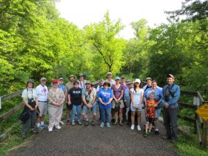 Birding by Ear participants stand on a trail in beautiful weather last summer.