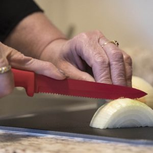 A woman's hands chop an onion on a black cutting board using a red knife.
