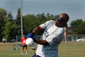 All beep baseball batters wear blindfolds and swing at the baseball, which makes a noise. Photo by New Bedford Guide.