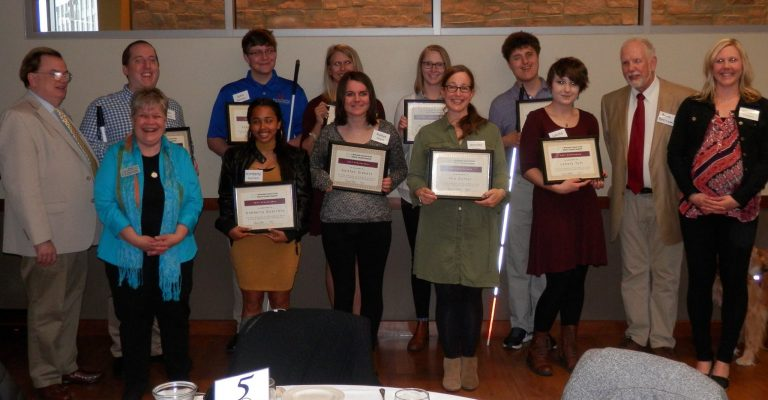 Scholarship recipients from 2017 hold their awards.