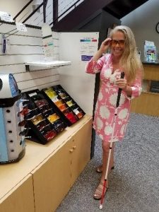 Wendi, a store customer, shops for a new pair of sunglasses. She faces the camera, with her right hand on the frame of a pair of sunglasses she has just put on as she holds her white cane in her left hand. She is dressed in a white and pink dress, has long blonde hair and is smiling. To her right are three displays of sunglasses in The Sharper Vision Store.