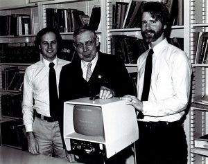 A black and white photo: Three men stand around a CCTV with bookshelves behind them.