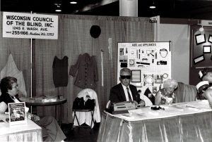A man and two women sit at a booth surrounded by adaptive products.