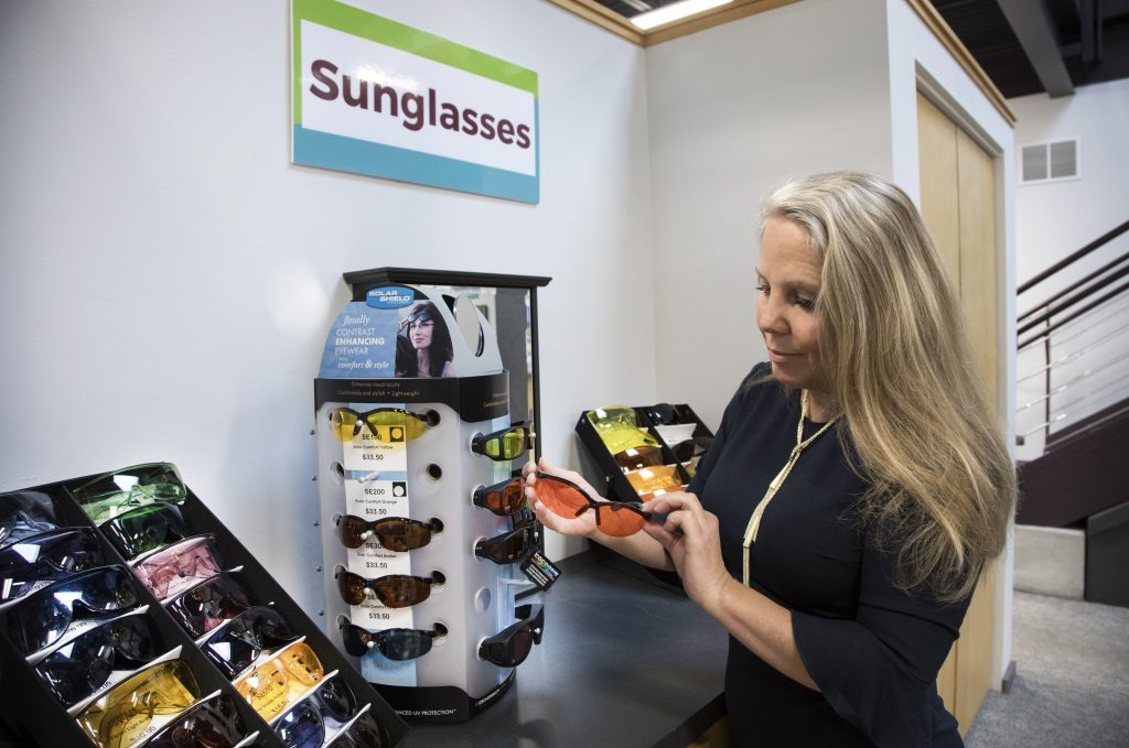 A woman stands in front of a sunglass display holding a pair of sunglasses.