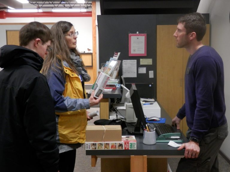 A man behind a cash register talks to a woman and her son. The mother is holding a store product.