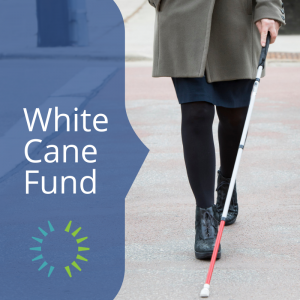 A woman walking toward the camera with a white cane in hand.