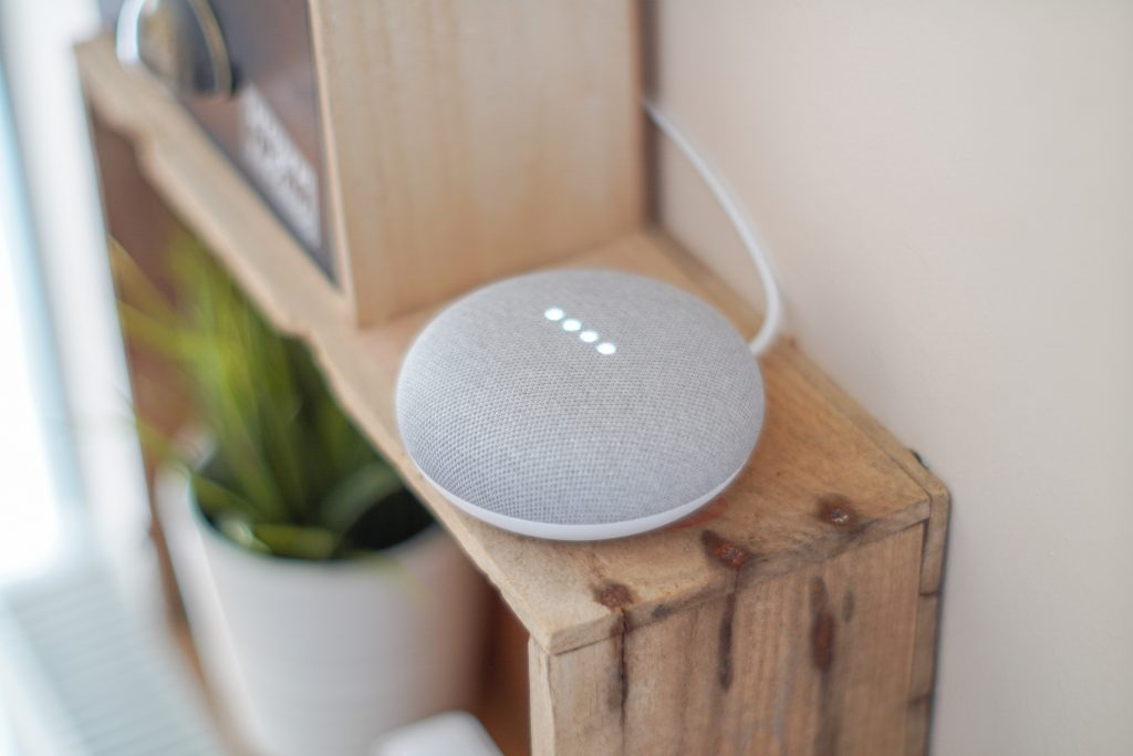 A round grey Google Home Mini speaker sits on a shelf.