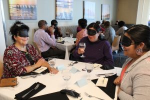 Three women who are blindfolded sit at a table.