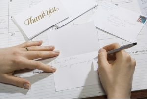 A hand writes thank you notes on a desk.