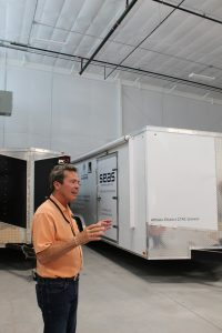 A man talking with his hands standing in front of a trailer.