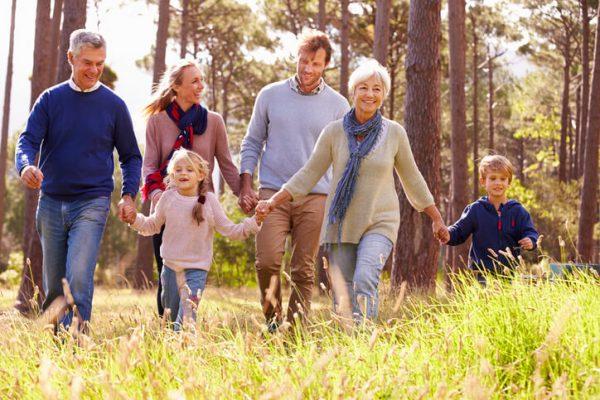 A multi-generational family walks outside.
