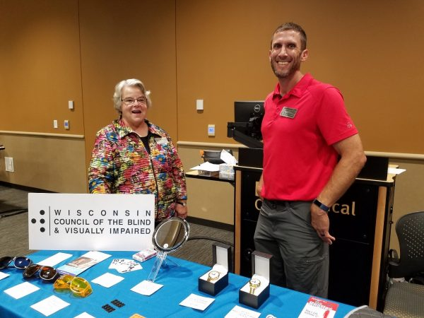 Two people stand at a vendor table with the Wisconsin Council of the Blind & Visually Impaired.