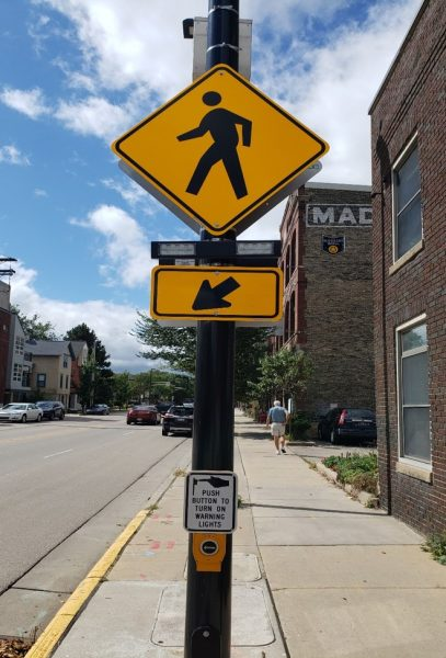 A yellow pedestrian sign and accessible pedestrian signal button.