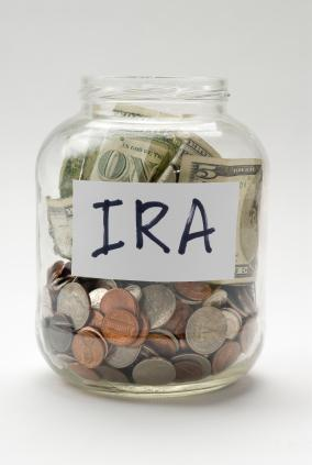 """A jar of money with an """"IRA"""" label on it."""