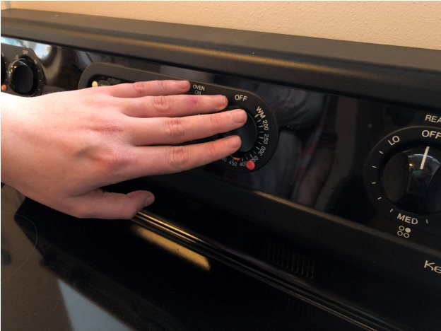 A hand touches a microwave button that is covered with an orange bump dot.