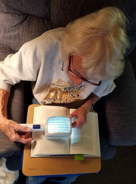 A woman reads a book using a magnifier.