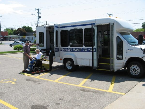 A paratransit rider in a wheelchair is helped out of a van.