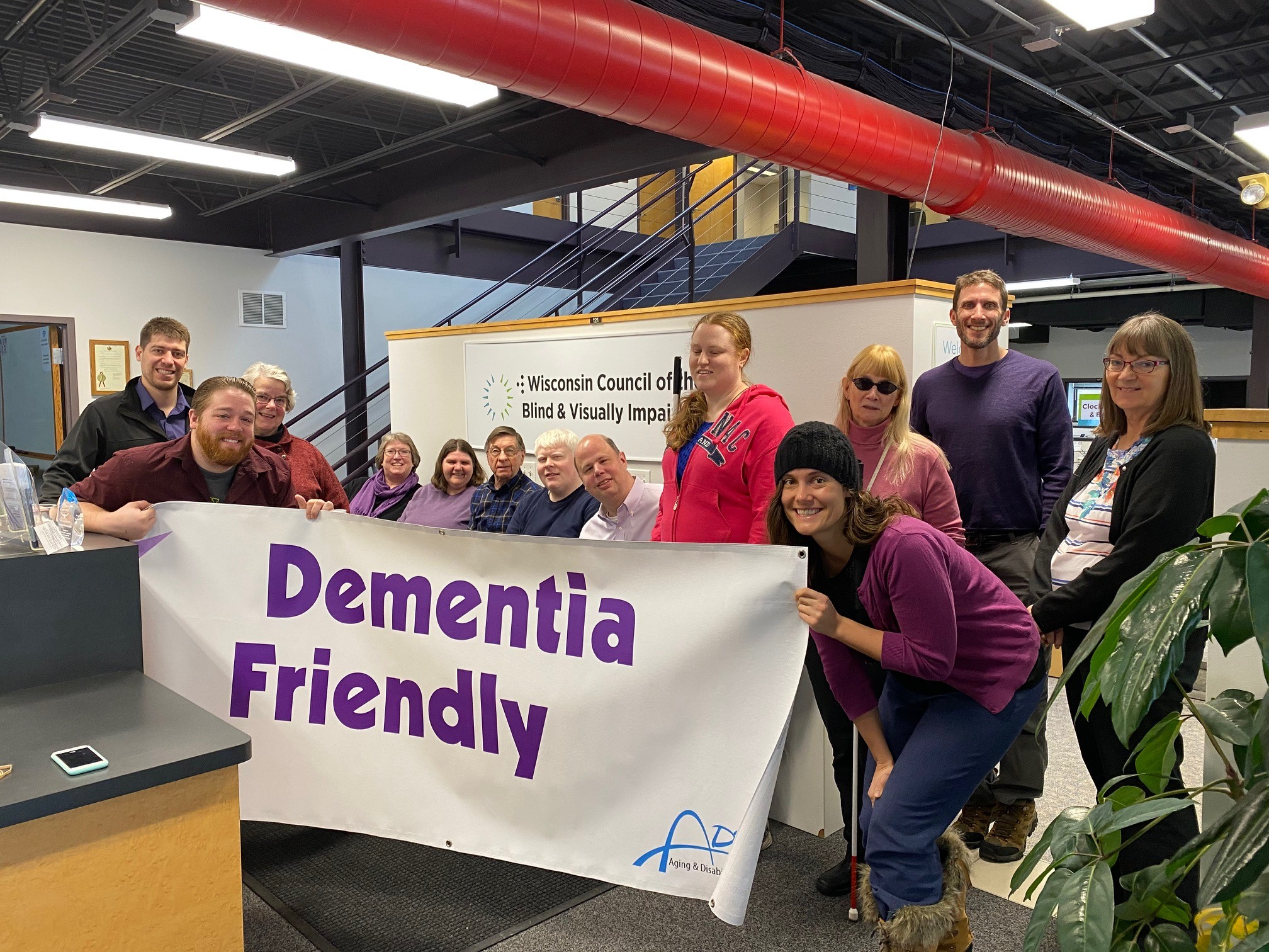 13 people standing in front of the WCBVI logo holding a Dementia Friendly banner.