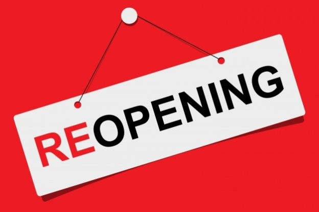 """A white sign on a red background that says, """"reopening"""" in red and black text."""