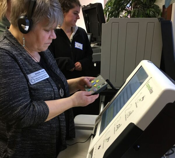 A woman using accessible voting equipment, wearing headphones and holding a tactile marking device