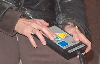A person's hands use an accessible voting machine.