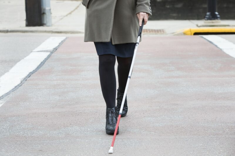 woman crossing street with cane