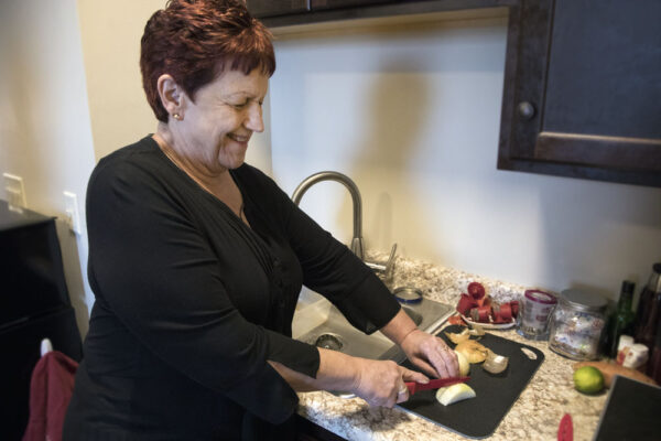 Council client Carol uses a high-contrast cutting board and safe slicing technique to slice onions in her apartment.