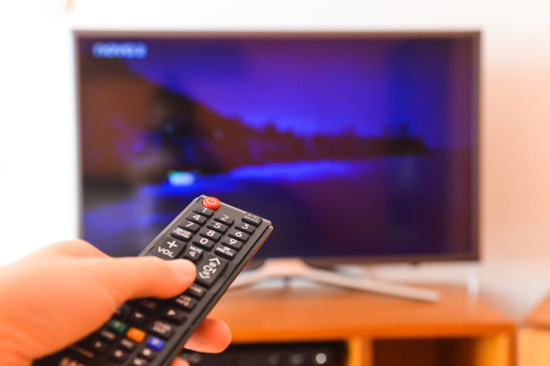 Hand pointing remote control at television
