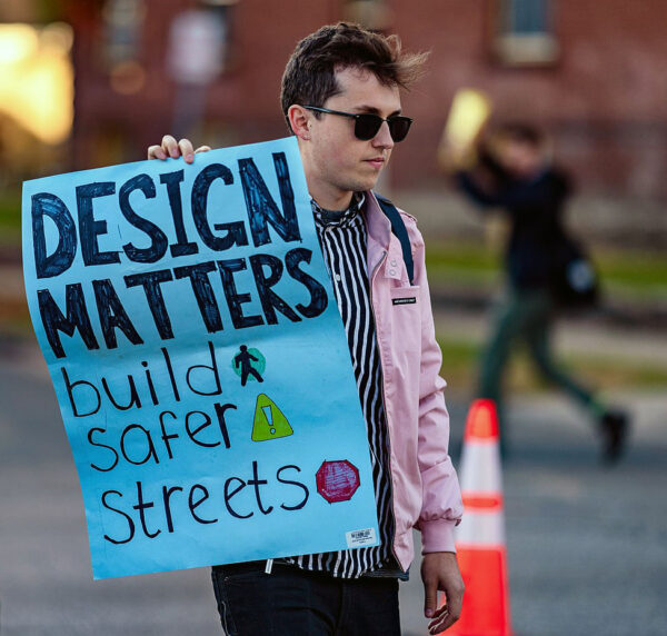 """Person holding sign that says """"design matters, build safer streets."""""""