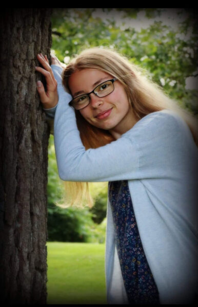 Girl leans on tree