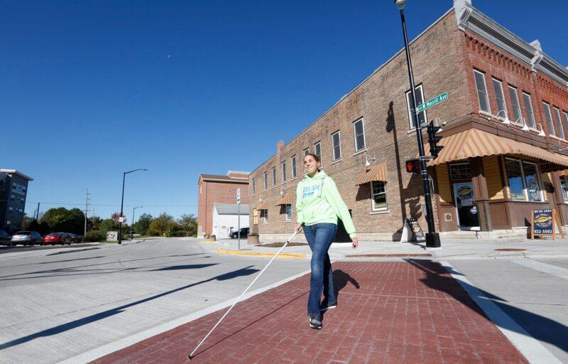 Woman crosses street using white cane.