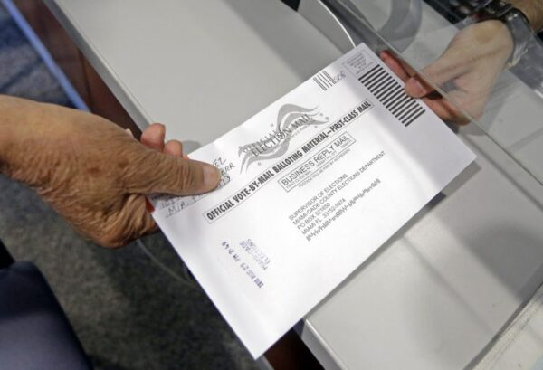 Absentee ballot is handed from one person to another.