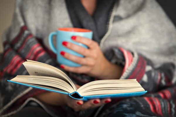 A person holding a mug of hot liquid in one hand and a book in the other.