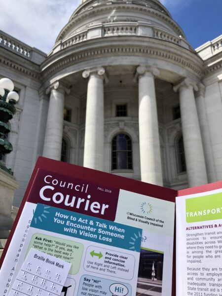 A folder containing a Council Courier, braille bookmark and a handout on transportation in front of the capitol building.