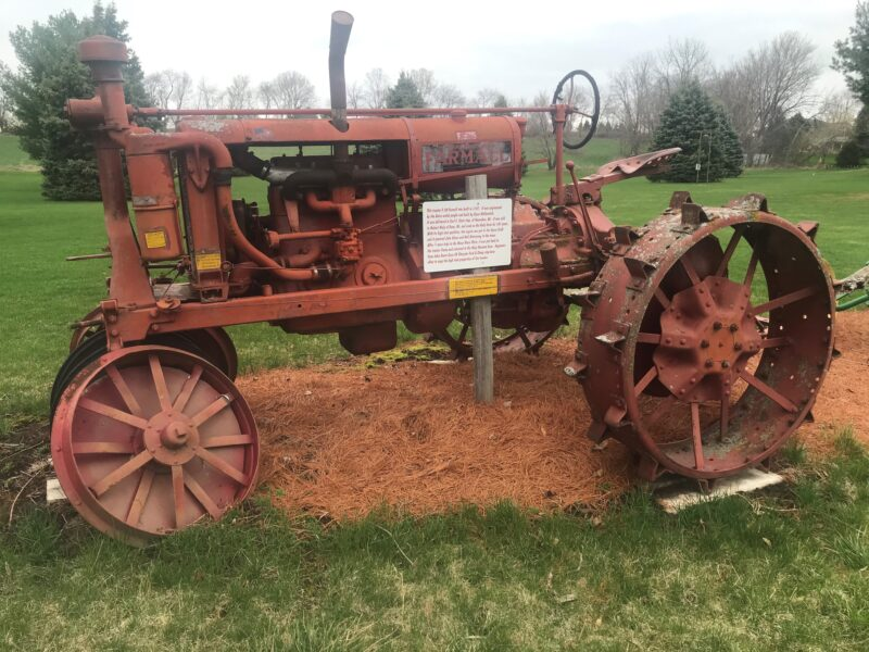"""An antique Farmall tractor on the Harvest Hills Golf Course containing a sign with a story that reads, in part: """"With its high tech qualities the engine was put in the Space Craft and it powered John Glenn and Neil Armstrong to the moon."""""""