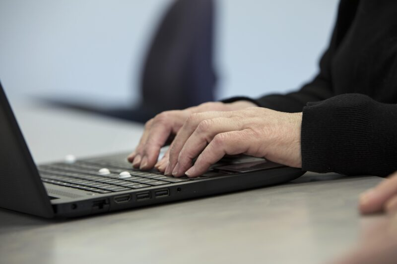 A person types on a laptop computer.