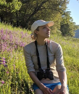 A woman with binoculars sits in a meadow as she listens to birds.