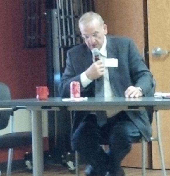 Wearing a business suit, Dan Sippl speaks into a microphone.