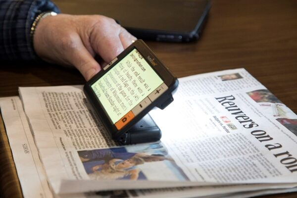 A magnifying device used by a person reading a newspaper.