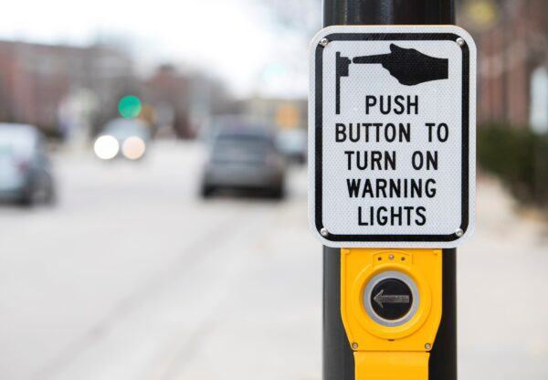 An Accessible Pedestrian Signal with large button and sign directing users to push to turn on warning lights.