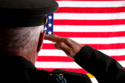 A man, wearing a military uniform, stands with his back to the camera, saluting a United States flag.