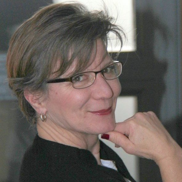 A woman with glasses holding chin smiling at the camera.