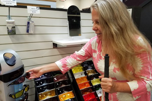 A woman selects from various shades of colored sunglasses at the Sharper Vision Store.